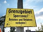 "Yellow sign mounted on a pole reading ""Grenzgebiet Sperrzone! Betreten und befehren verboten!"""