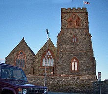 A stone church seen from the west with a broad battlemented tower