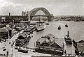 Sydney harbour ferries in Circular Quay with almost complete Sydney Harbour Bridge probably early 1932 or late 1931.jpg