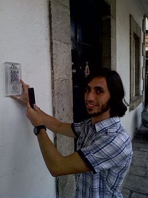 Gibraltarpedia - Gibraltarpedia coordinator Tyson Lee Holmes with trial plaque containing QR code.