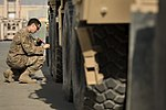 U.S. Air Force Staff Sgt. William Voorheis, an aerial porter with the 455th Expeditionary Aerial Port Squadron, checks the tire pressure on a light medium tactical vehicle during a joint inspection at Bagram 131002-F-YL744-054.jpg