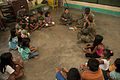 U.S. Marine Corps Maj. Grace Janosek, second from top right, with the III Marine Expeditionary Force civil affairs element, reads to children as they wait to be seen by Philippine and U.S. military doctors 130405-M-UY788-097.jpg
