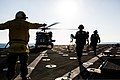 U.S. Navy Boatswain's Mate 2nd Class Quincy Smith, left, waits for Sailors to clear the flight deck after removing chocks and chains from an Army UH-60 Black Hawk medevac helicopter assigned to Charlie 131226-Z-AR422-087.jpg