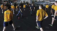 U.S. Navy Master-at-Arms 1st Class Sara Horvath, center left, and Master-at-Arms 2nd Class John Kuchler, center, lead Sailors in physical fitness training aboard the aircraft carrier USS Nimitz (CVN 68) June 27 130627-N-TX484-018.jpg