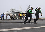 U.S. Sailors move out of the landing area after checking the arresting gear during flight operations aboard the aircraft carrier USS Nimitz (CVN 68) in the Gulf of Oman June 19, 2013 130619-N-GA424-172.jpg