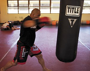 "Punching bag - A mixed martial arts fighter ""working his hands"" on a heavy bag"