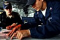 US Navy 050726-N-5549O-107 Quartermaster 3rd Class Chris Wright discuss with the Officer of the Deck, Lt. Terra McIntyre a recommended course for navigation aboard USS Ronald Reagan (CVN 76).jpg