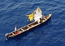 vue en plongée de deux hommes dans une pirogue longue et étroite
