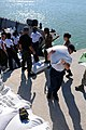 US Navy 080915-N-7955L-110 ailors embarked aboard the amphibious assault ship USS Kearsarge (LHD 3) move bags of rice off a landing craft during a humanitarian assistance mission in Haiti.jpg