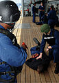 US Navy 090430-N-0046R-035 Ship's Serviceman Seaman Jimmy Roberts and Operations Specialist 3rd Class Gareth Pontd apprehend a role-player depicting a suspected terrorist during an anti-terrorism force protection drill.jpg