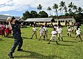 US Navy 110418-F-HS649-291 Musician 3rd Class Stephen Weninger throws a rugby ball while playing with Tongan children before a ribbon cutting cerem.jpg