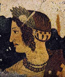 Fresque de couleur noire, ocre, verte et rouge montrant un visage de femme avec une couronne d'olivier, des cheveux longs et bouclés et deux colliers.