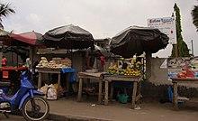 på en gata, två träbåsar, skyddade av ett parasoll, lutar sig mot en vägg och presenterar bröd för den ena och frukt för den andra