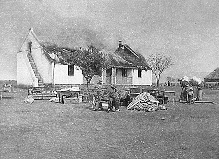One British response to the guerrilla war was a 'scorched earth' policy to deny the guerrillas supplies and refuge. In this image Boer civilians watch their house as it is burned. VerskroeideAarde1.jpg