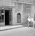 Vrouw met twee kinderen aan de hand en pakket onder haar arm geklemd lopend over, Bestanddeelnr 255-2478.jpg
