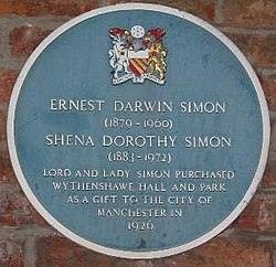 "A circular plaque coloured blue mounted on a brick wall, containing the coat of arms of Manchester City Council at the top, the white text ""Ernest Darwin Simon (1879–1960)"" and ""Shena Dorothy Simon (1883–1972)"" in the centre, followed by ""Lord and Lady Simon purchased Wyhtenshawe Hall and Park as a gift to the City of Manchester in 1926"""
