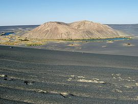 A white hill within a black depression, with lakes and vegetation at its foot and desert elsewhere