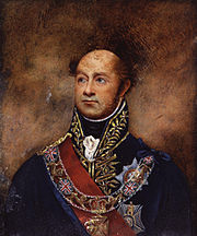 Painting shows a bald man in a high-collared dark blue military uniform with much gold braid. He wears a red sash and a number of decorations.