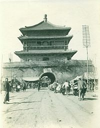 An old black and white picture of the Bell Tower with a lot of Chinese people in traditional clothes.