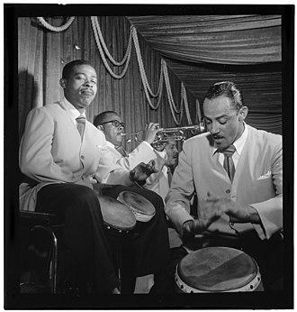 Carlos Vidal Bolado - Carlos Vidal on conga (right) playing alongside José Mangual on bongos (left) and trumpeter Mario Bauzá (center) at the Glen Island Casino, New York, 1947.