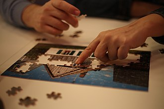 Jigsaw puzzle - People solving a jigsaw puzzle