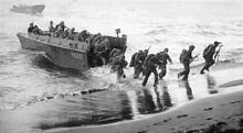 black & white photograph of Marines disembarking a landing craft at a beachhead