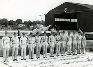 3d Fighter Training Squadron - Officers of the 3d Pursuit Squadron in formation in front of a squadron Boeing P-26 Peashooter, Clark Field, Luzon, Philippines, 1937.