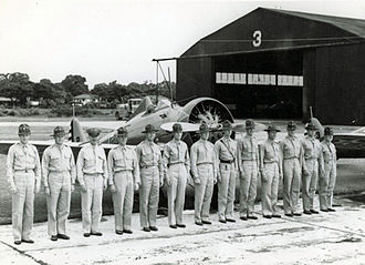 4th Composite Group - Officers of the 3d Pursuit Squadron in formation in front of a squadron Boeing P-26 Peashooter, Clark Field, Luzon, Philippines, 1937