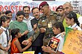 A schoolgirl tying Rakhi to an Army Jawan in New Delhi on August 02, 2017. The Minister of State for Defence, Dr. Subhash Ramrao Bhamre is also seen.jpg