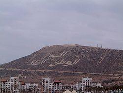 La Casbah d'Agadir (Dénommée Agadir Oufella en tachelhit, c'est-à-dire Agadir-d'en-Haut) vue depuis la plage (inscriptions:Dieu, la Patrie, le Roi)