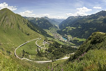 Photo of a looping road on the approach to Gotthard Pass with the town of Airolo in the distance.