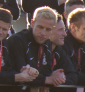 Blond Andrew Davies, leaning on a railing in a crowd