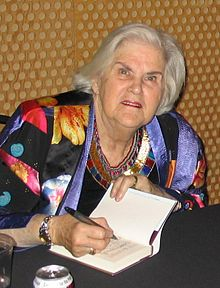 A woman with white hair wearing a light black and multicoloured jacket is seated at a table signing a book