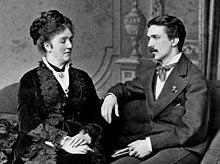 Fotografie pozată reprezentând Arcadia Claret și fiul său Arthur așezați pe o canapea