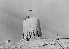 Soldiers stand at the base of a sandstone structure in the desert whilst a flag is unfurled on top of the building