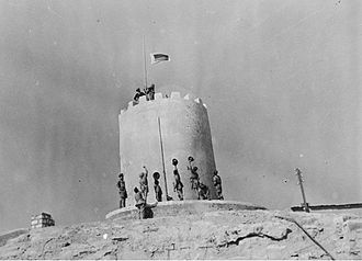 2/9th Battalion (Australia) - Soldiers from the 2/9th hoist a flag consisting of the battalion's Unit Colour Patch over the recently captured Italian fort at Giarabub.