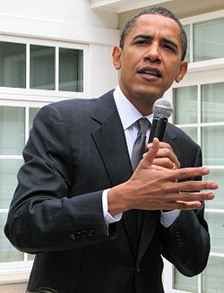 Picture of a man holding a microphone and talking and gesturing
