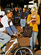 Blonde woman with tattoos texting on street.jpg