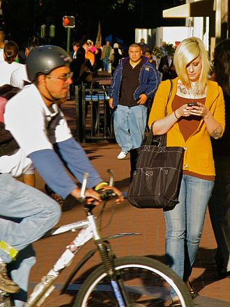 Smartphone zombie - Image: Blonde woman with tattoos texting on street