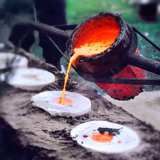Benin Bronzes - Modern-day view of bronze casting using the lost wax method. The molten metal is poured into the mold.