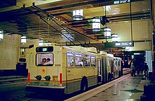 A white bus with raised poles stopped at the curb of an underground station. The granite-tiled floors reflect bright lanterns placed above the platform, adjacent to an upper level walkway.