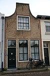 foto van Huis met geverfde tuitgevel met oorspronkelijke gesneden deur