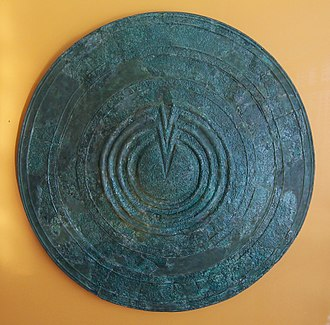 Shield volcano - An Ancient Greek warrior's shield–its circular shape and gently sloping surface, with a central raised area, is a shape shared by many shield volcanoes.