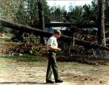 Governor Carroll walking among downed trees