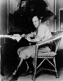 DeMille posing on a chair with a pen in hand