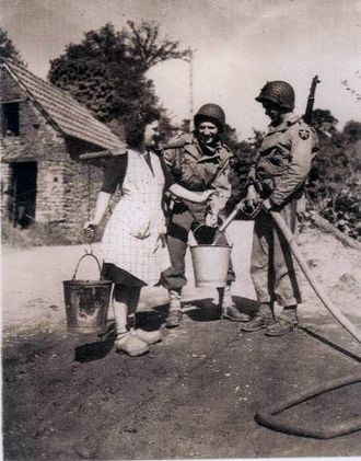Cerisy-la-Forêt - Two American soldiers helping a young farmer from Cerisy-la-Forêt: This photo made the front page of The New York Times in June 1944.