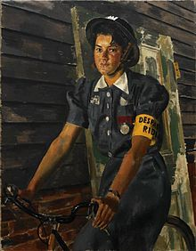 A girl in ARP uniform, wearing a tin helmet and riding a bike