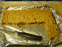 A foil-lined tray with a solid light brown sheet with dark brown spots. A section has been cut away and most of a knife is lying in that portion.