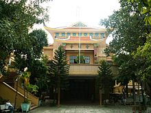De voorkant van de pagode is crèmekleurig en staat op een verhoogd platform dat via een trap met de grond is verbonden.  Chinese karakters zijn boven een reeks sierlijke glazen ramen.  Een paar mensen zitten op de banken in de bakstenen binnenplaats beneden, omgeven door veel bomen en struiken.  Het dak is bruin betegeld en er is een ongebruikte vlaggenmast aan de voorzijde van het hefplatform.
