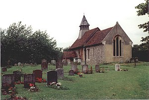 A small stone church with red tiled roofs seen through a churchyard from the southeast.  On its far gable is a bellcote with a pyramidal roof
